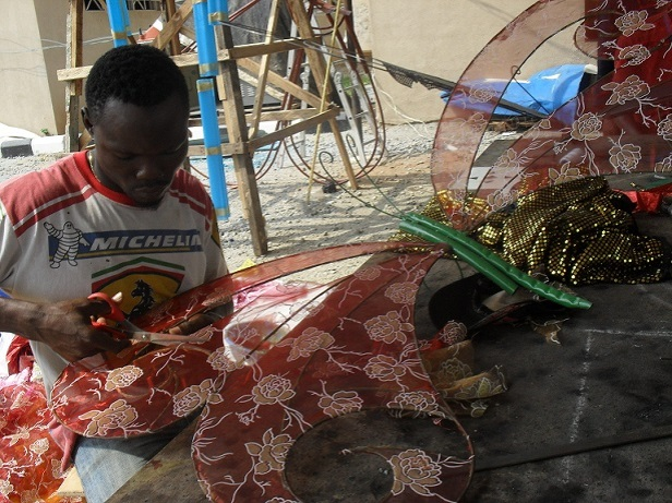 a young artisan working on a butterfly effigy