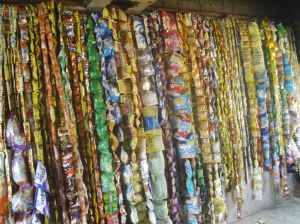 An installation by Lanre Tejuoso showing disused wraps of sweets, beverage and biscuits