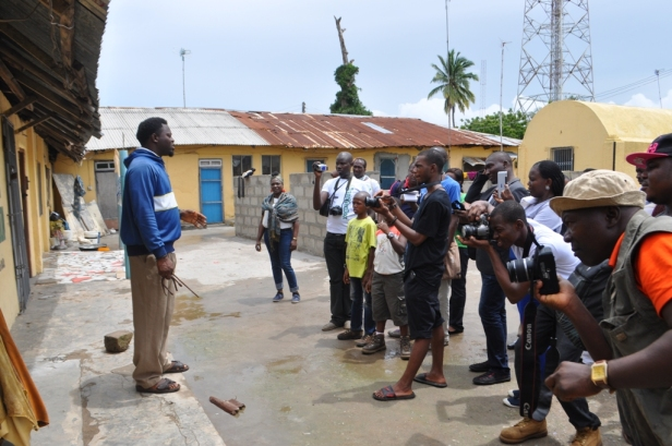 """One of Badagry's resourceful and tourist guide Anago James Akeem Osho lectures tourists about slavery in the compound that once housed 40+ slave cells known as """"Brazillian Baracoons"""""""