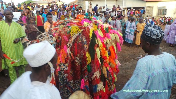 The Osokia'a masquerade surrounded by a jubilant crowd of celebrants